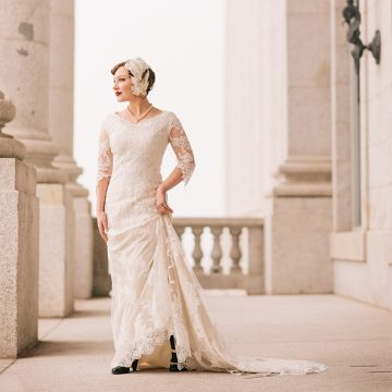 A bride standing in front of columns at the Utah State Capitol for bridal photography in Utah.