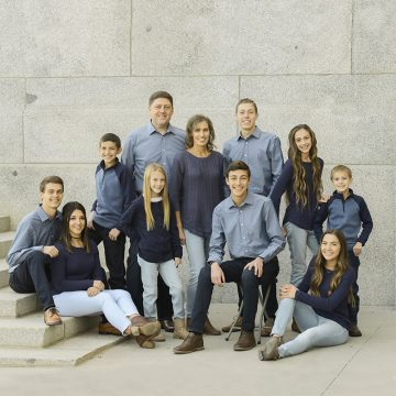 Family sitting on the steps of the Utah State Capitol for family photography in Utah.