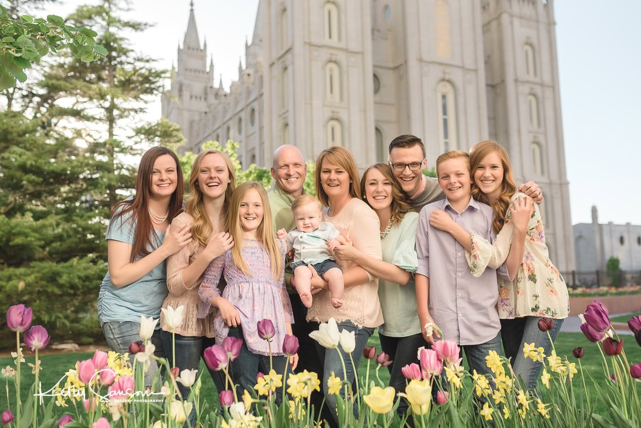 A family snuggling in front of tulips by the Salt Lake Temple for family photography in Utah.