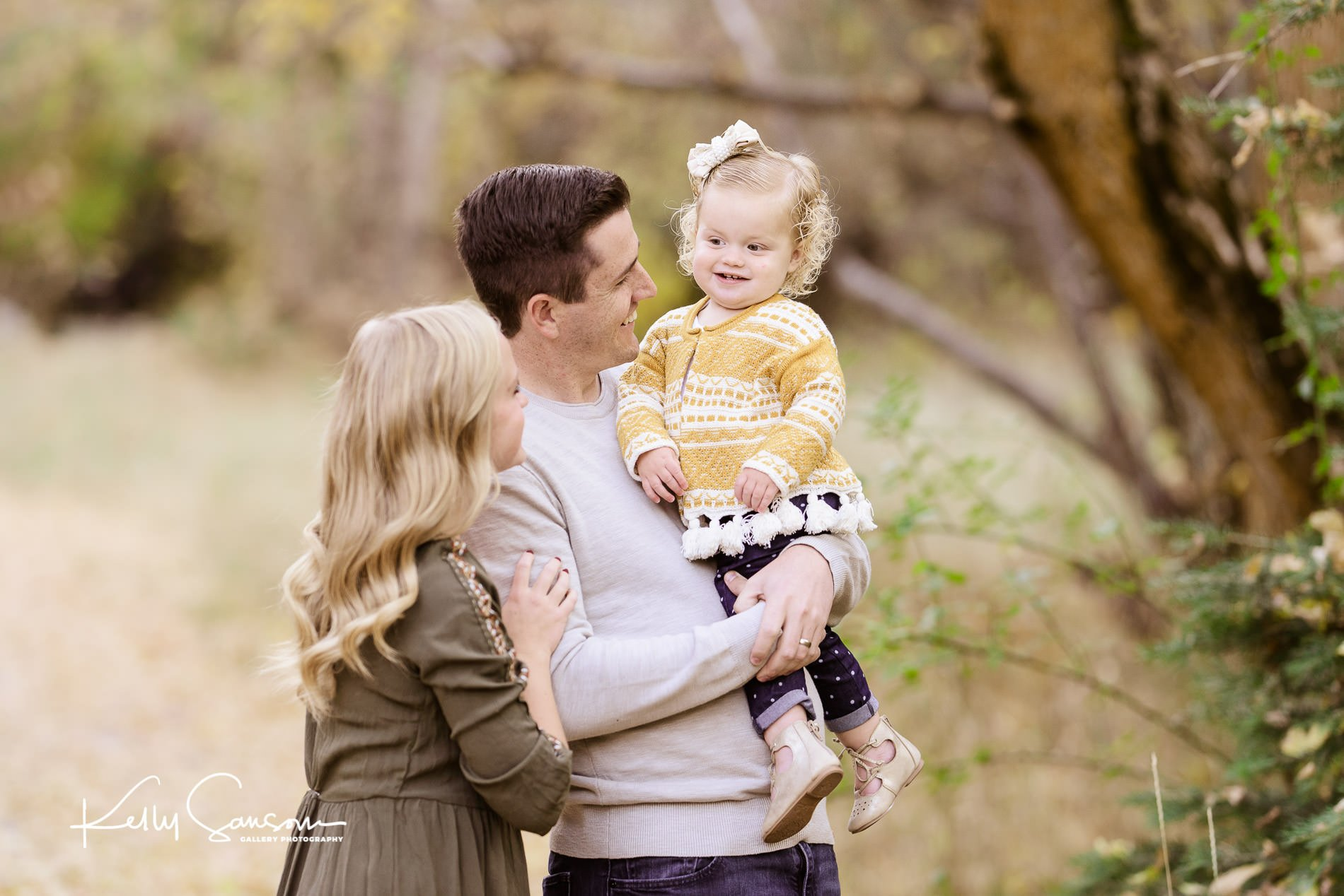 Couple holding baby girl in the mountains for bountiful family photography.