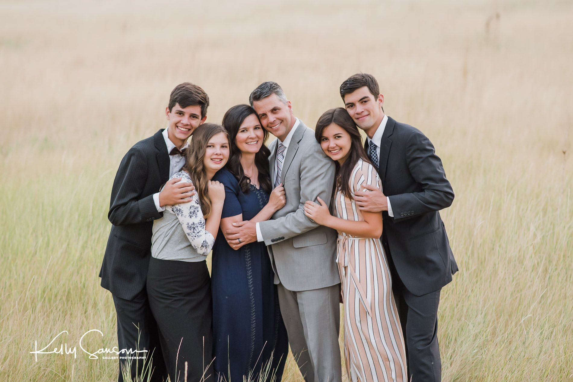 A family snuggling together in tall grasses for Bountiful portrait photography.