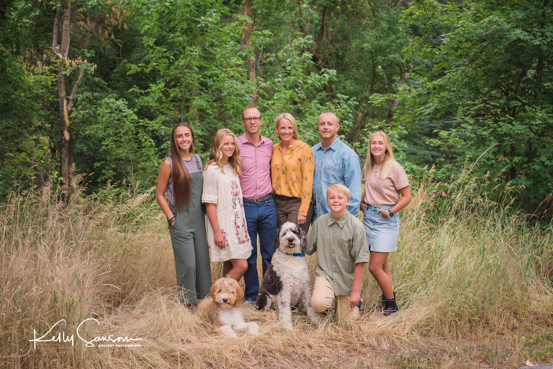 A family with dogs in front of trees for Bountiful portrait photography.