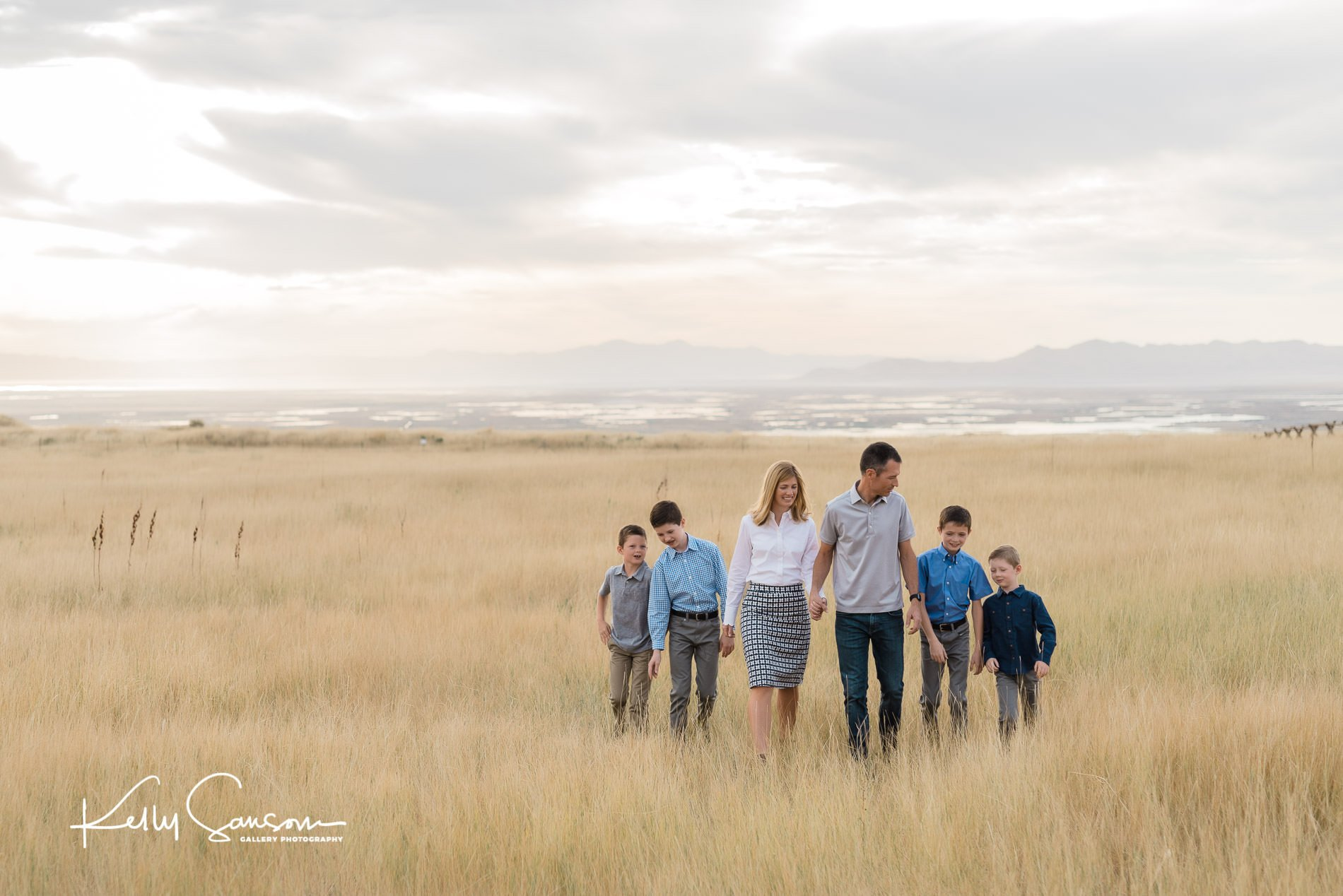 A family holding hands walking through tall grasses with view in the background for Bountiful portrait photography.