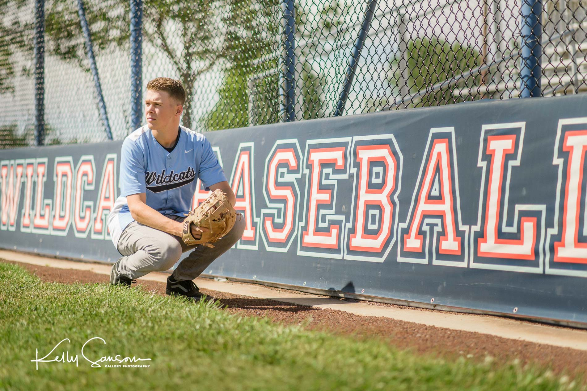 A high school in his baseball uniform kneeling on the field for Bountiful senior photography.