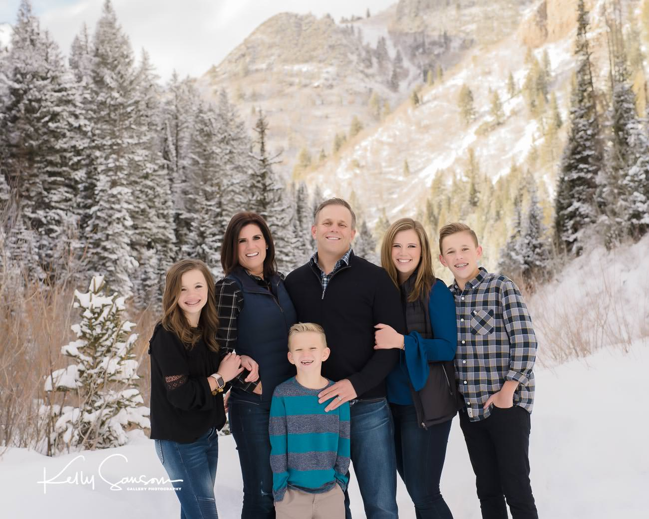 family snuggling together with snowy pines and mountain behind winter family photography at Jordan pines.
