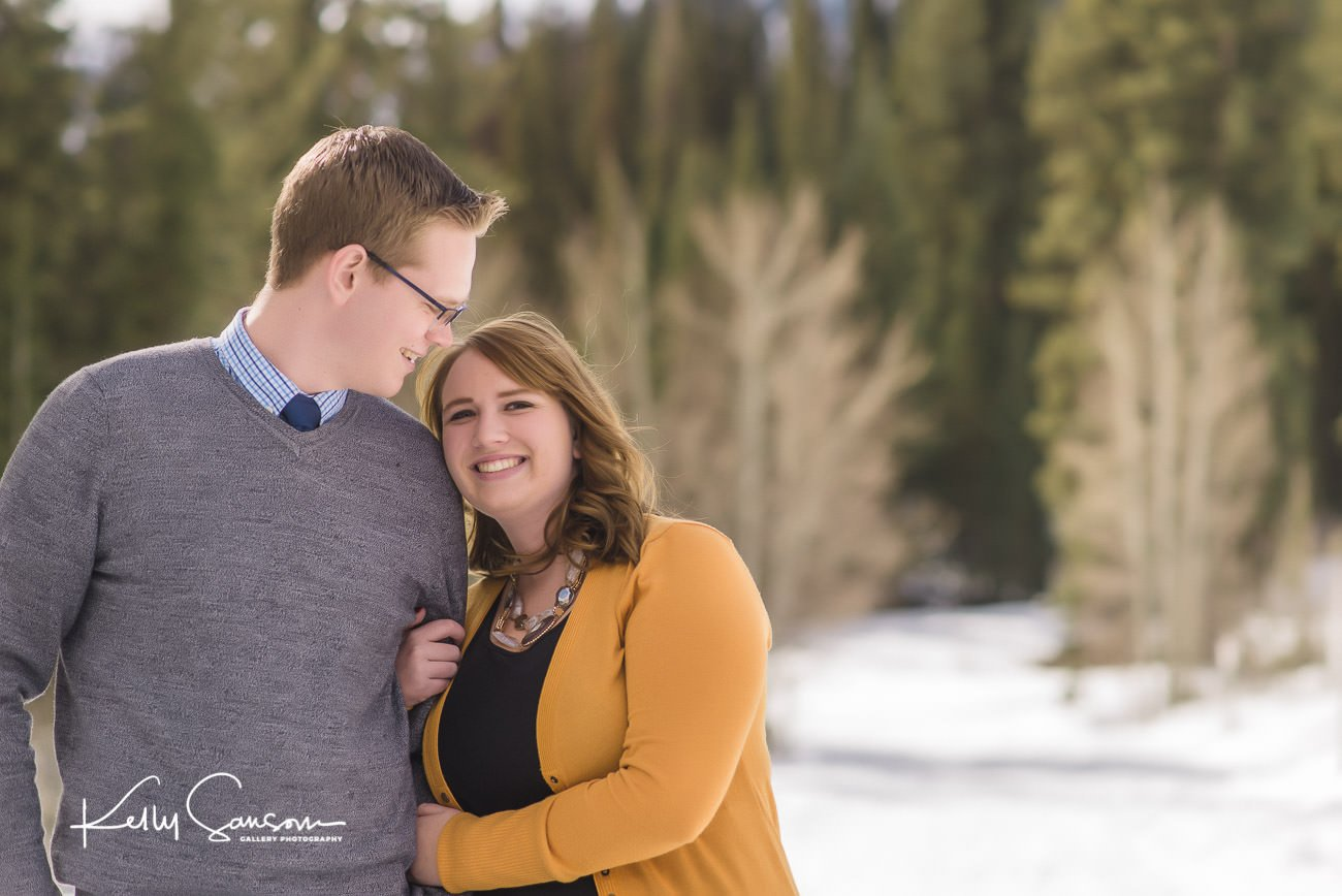 girl snuggling into man as he looks at her in snowy engagement photography at Jordan pines.