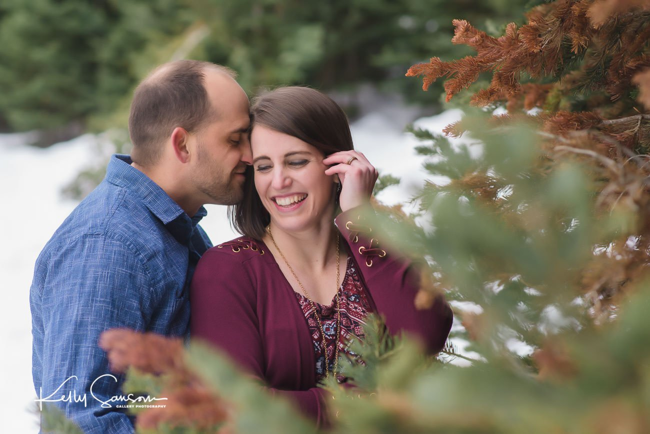 groom snuggling into bride by pine tree in snowy engagement photography at Jordan pines.