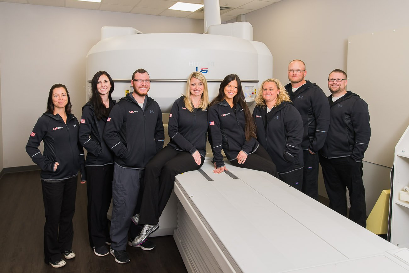 A team of MRI professionals stand in front of an MRI machine for Ogden commercial photography.