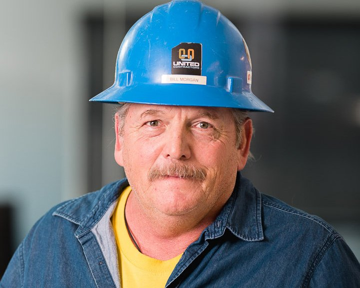 A man with a hardhat smiles at the camera for Ogden commercial photography.