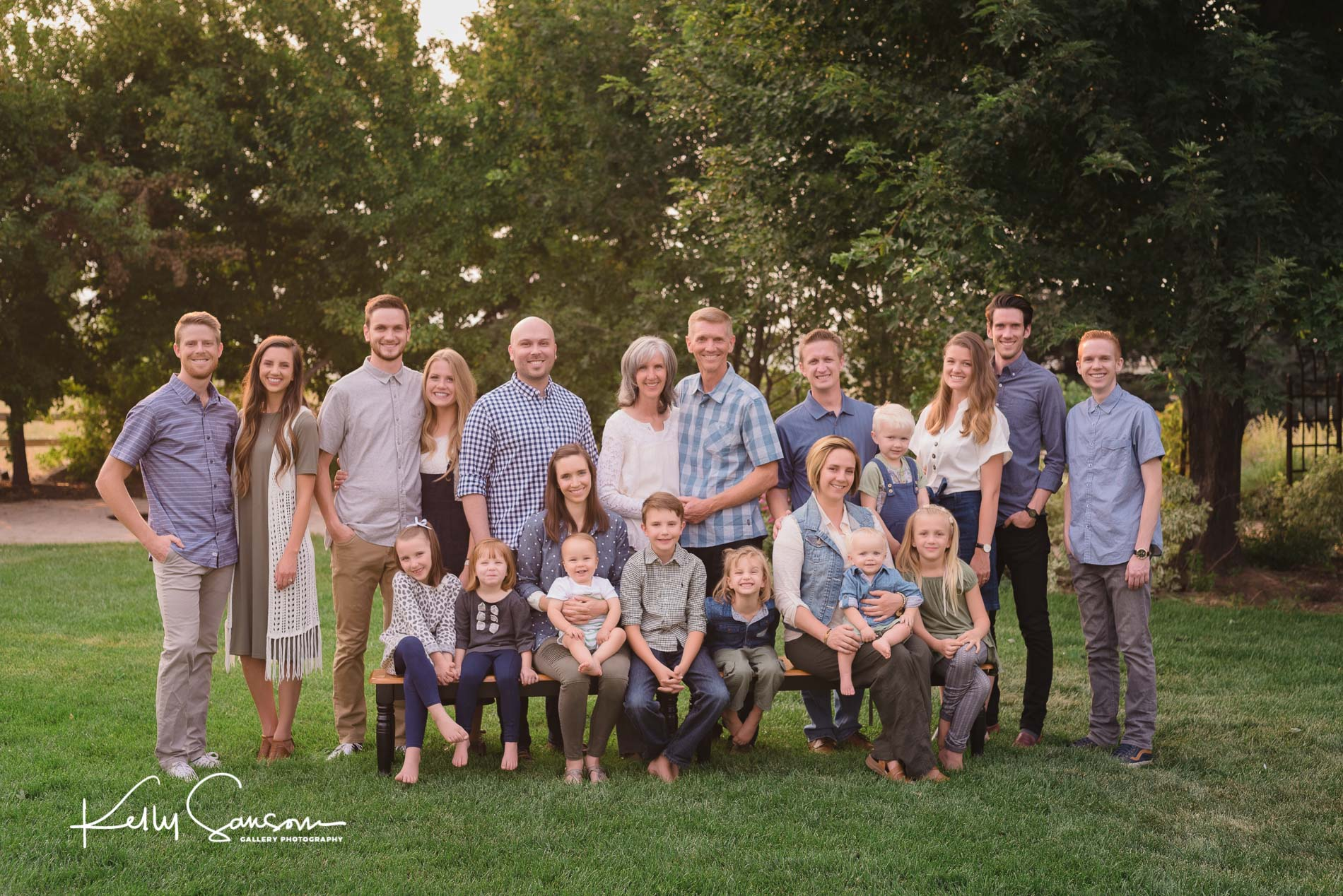 Large family group looking at camera with trees behind on grass for Ogden family photography.