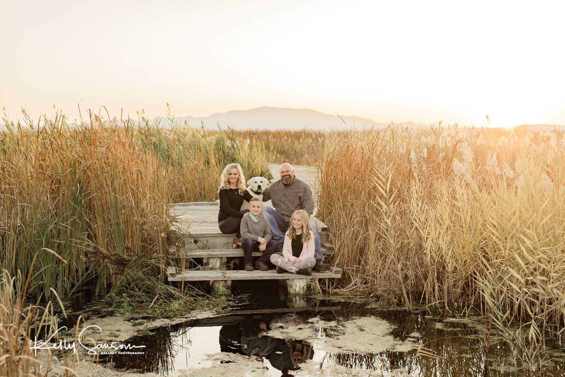 Family sitting on wooden steps that lead to a pond for Ogden family photography.