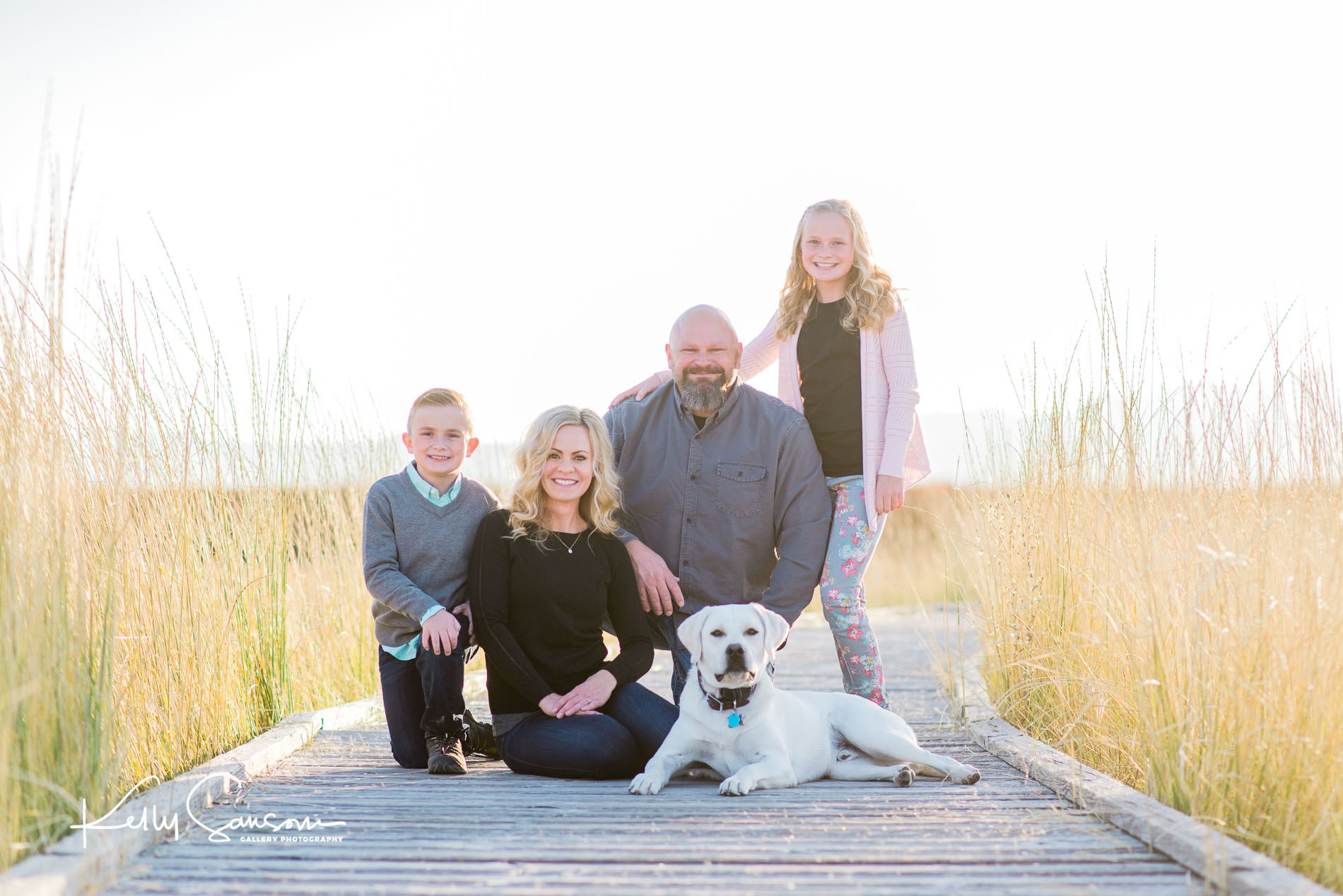 Family with dog sitting on boardwalk with talk grasses all around for Ogden family photography.
