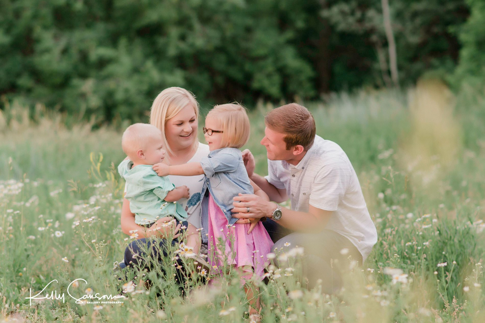 A young family playing with a dandelion in tall grass for Ogden portrait photography.