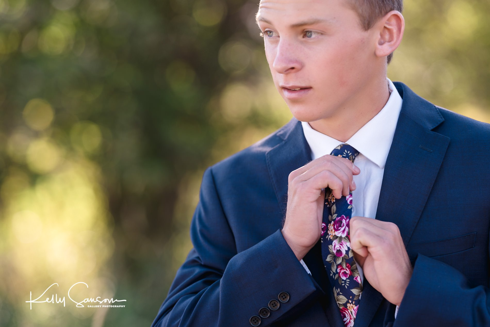 High School senior boy tying his tie for Ogden senior photography.