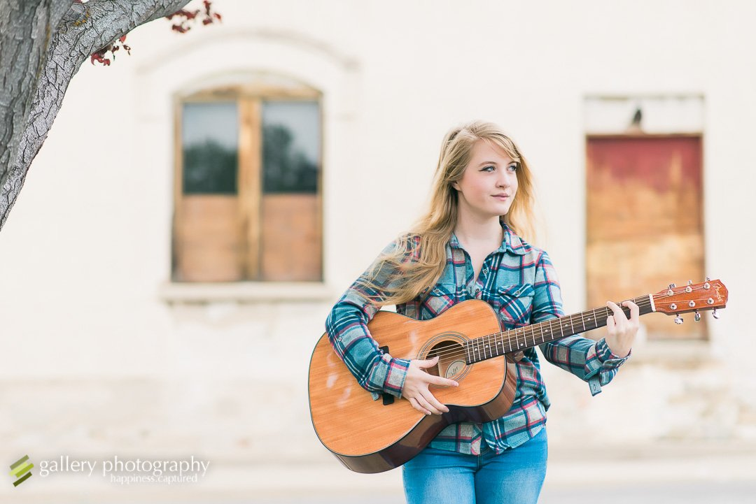 A high school senior girl holding a guitar in front of a dilapidated building for Ogden senior photography.