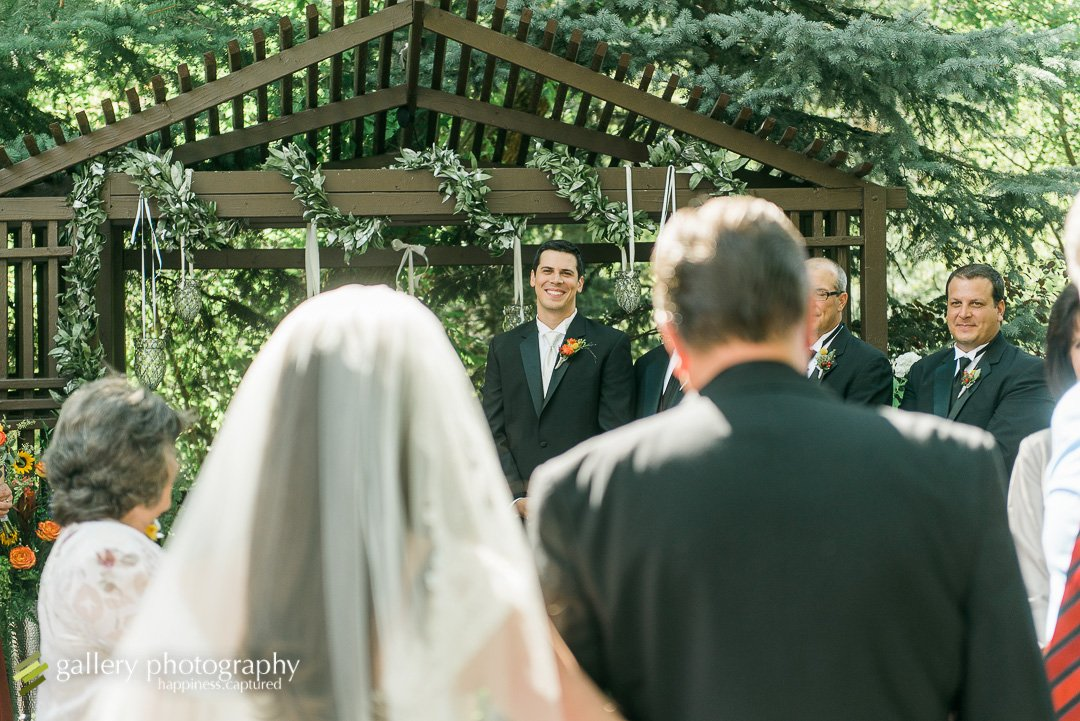 A groom smiling seeing his bride for the first time walking down the aisle for Ogden wedding photography.