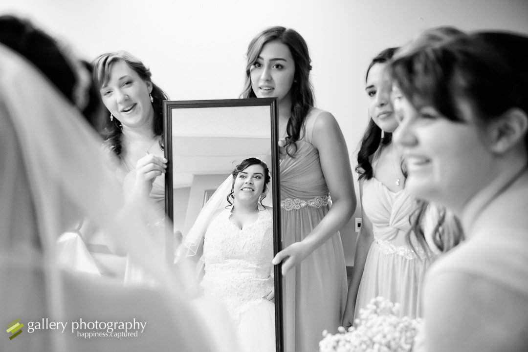 A bride looks in a mirror held by her bridesmaids for Ogden wedding photography.