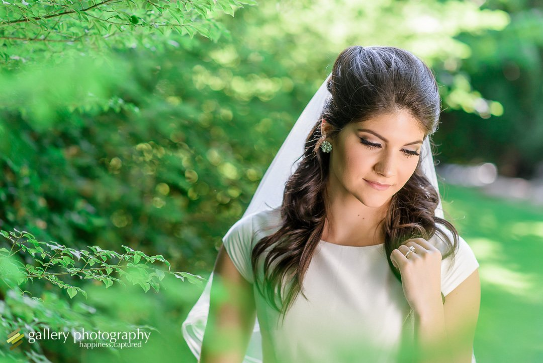 Bride looking down with bushes in foreground for bridal photography at Garden Park Ward.
