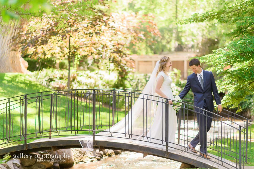 Groom leading bride across bridge for wedding photography at Garden Park Ward.