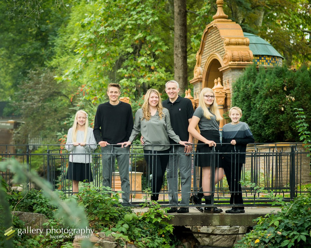 Family by railing near river for family photography at Garden Park Ward.