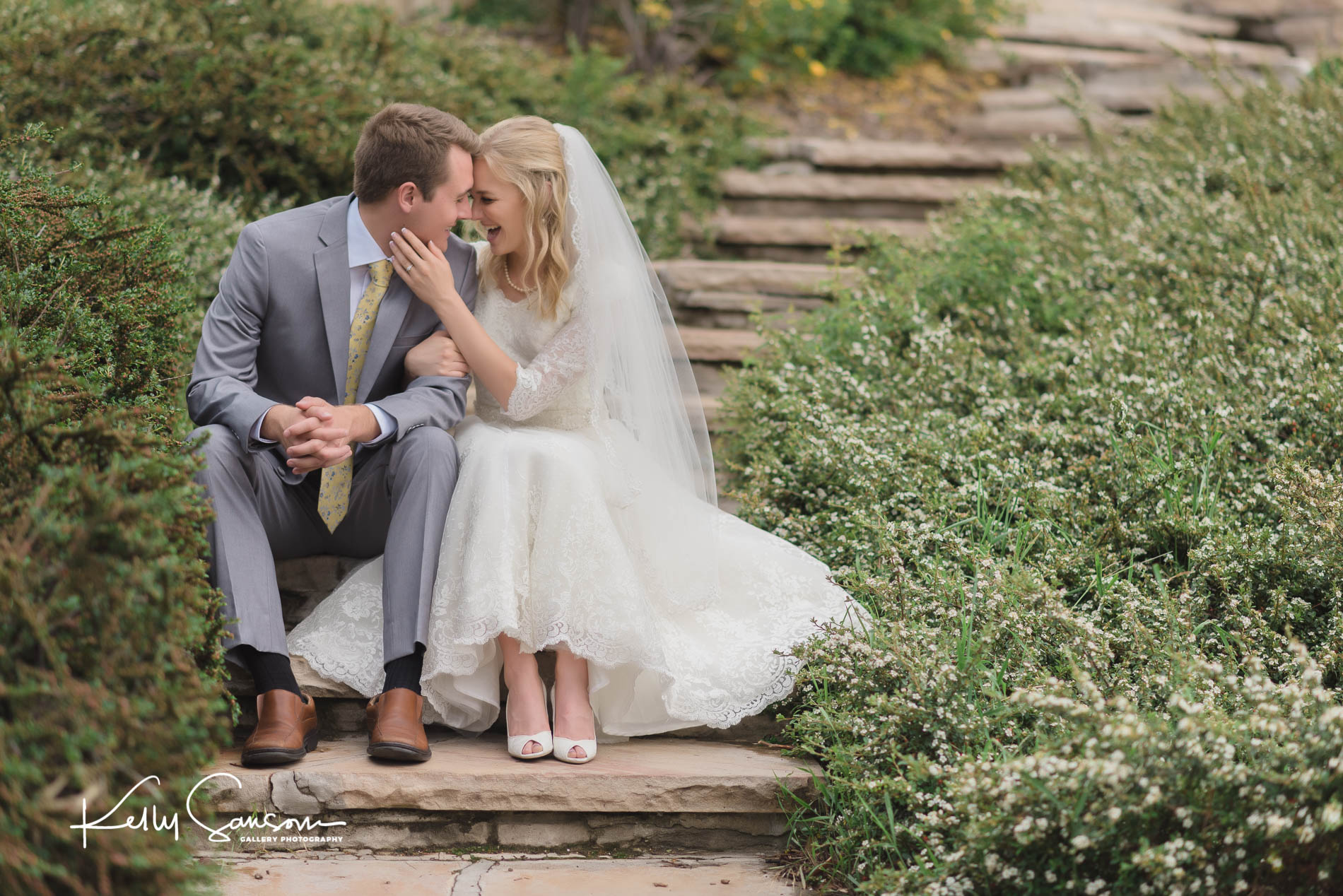 A bride and groom sitting on steps for bridal photography at Memory Grove.