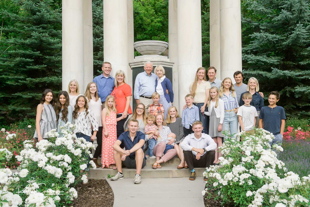 A large extended family posed on a monument for large family photography at Memory Grove.