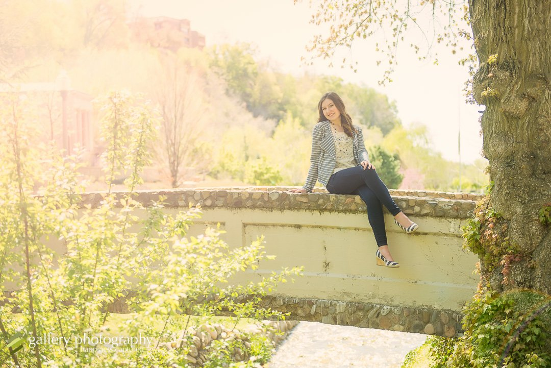 A senior girl sitting on a bridge for senior photography at Memory Grove.
