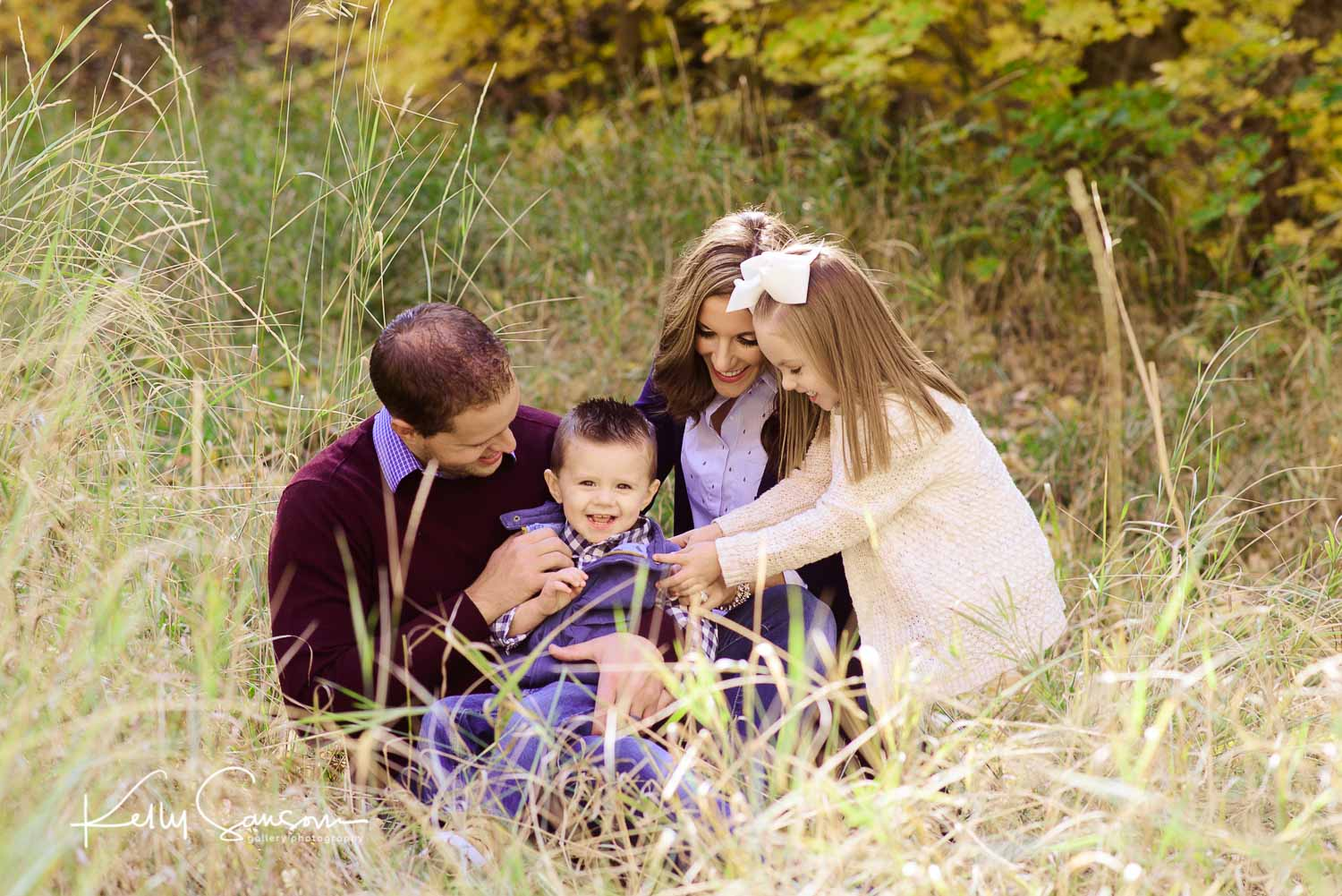 A small family tickling each other in tall grass for family photography at Mueller Park.