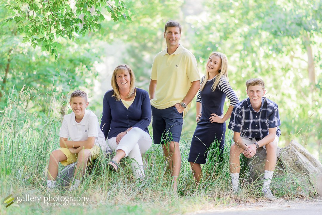 A family sitting on rocks in front of grasses and trees for family photography at Mueller Park.