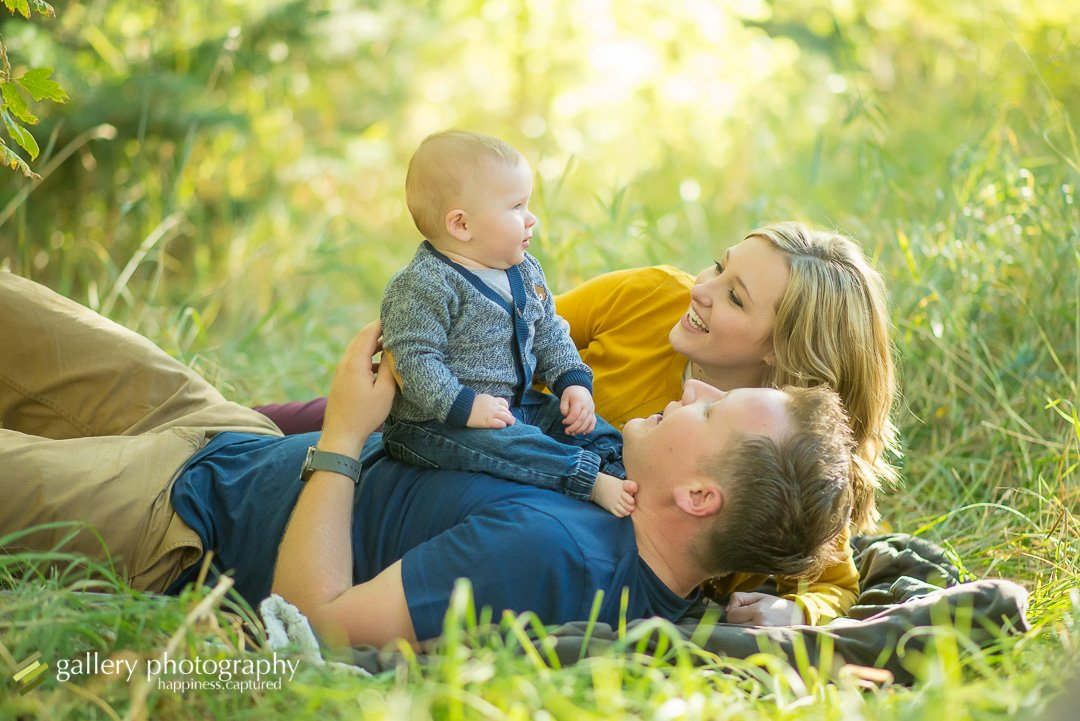 A couple laying on their backs with their baby boy on their chests with trees behind them for family photography at Mueller Park.