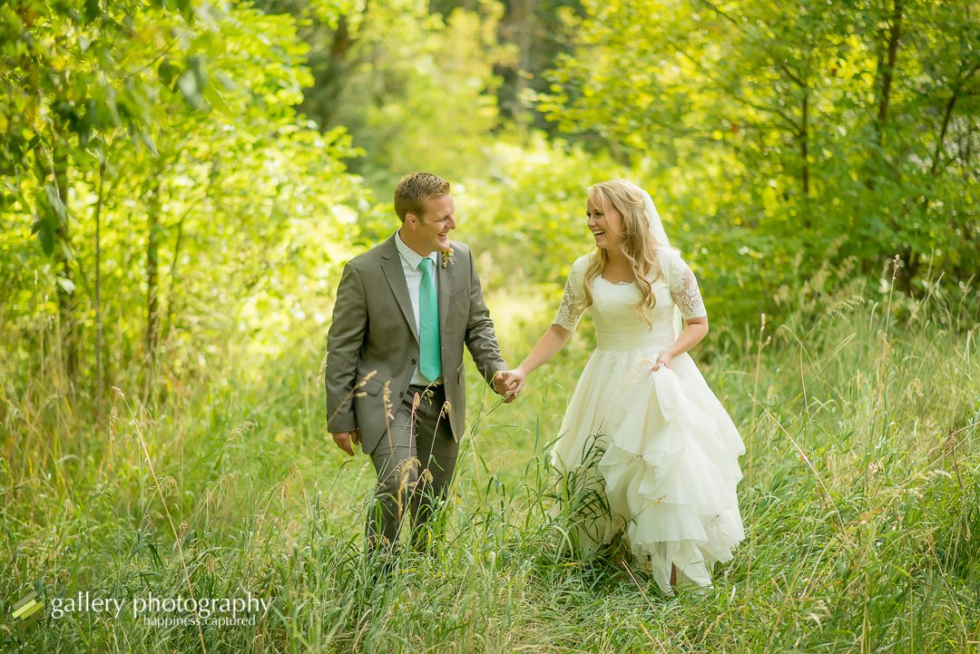 A bride and groom walking through tall grasses for wedding photography at Mueller Park.