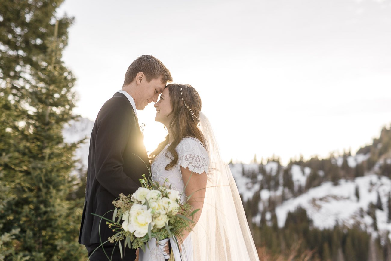 A bride and groom touching foreheads together with the sun and snowy mountains in the background for wedding photography at Silver Lake.