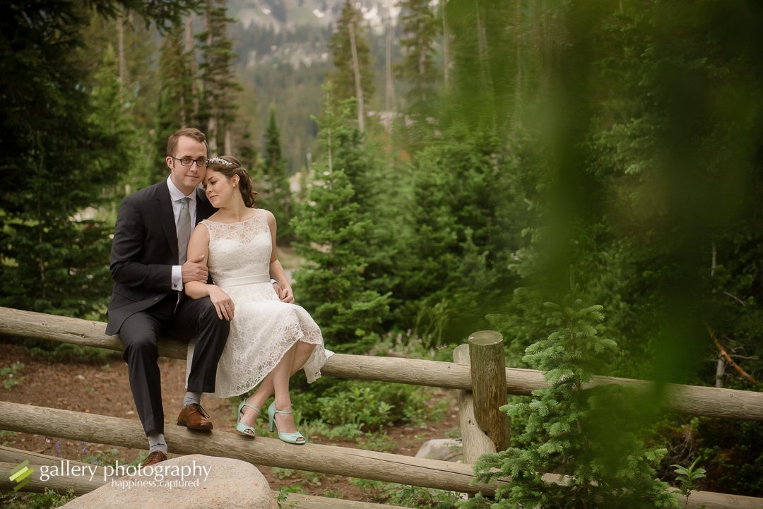 A bride and groom sitting together snuggling on a log fence for wedding photography at Silver Lake.