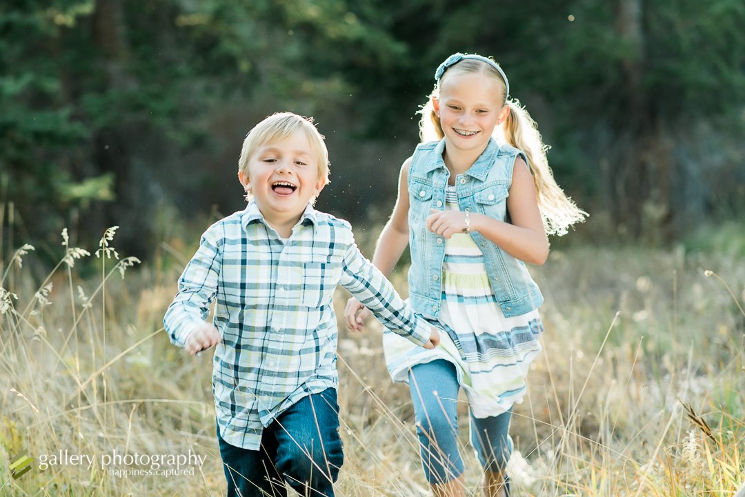 A brother and sister running towards the camera with pine trees behind for family photography at Silver Lake.