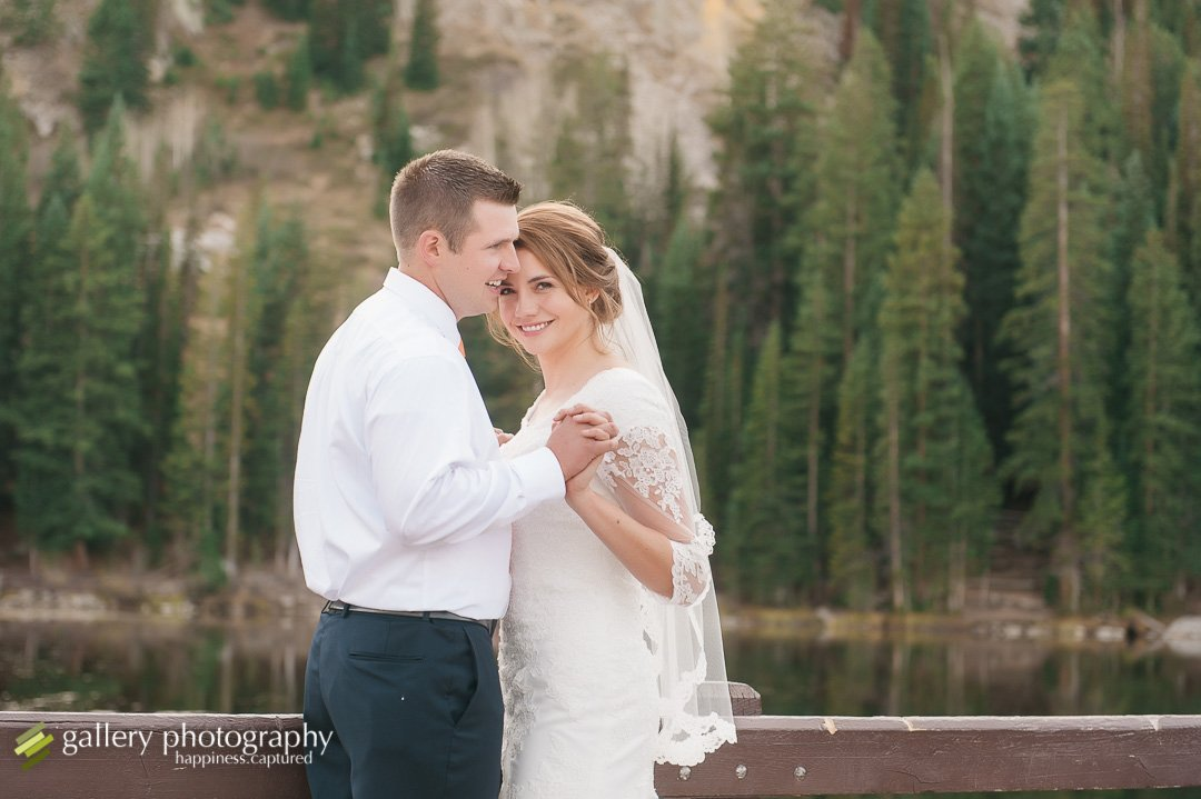A bride and groom holding hands snuggling with a mountain lake and pine trees behind for wedding photography at Silver Lake.