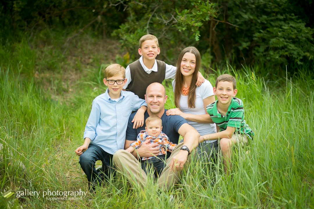 Family sitting in grasses with oak trees in the background for family photography at Temple Rock Quarry.