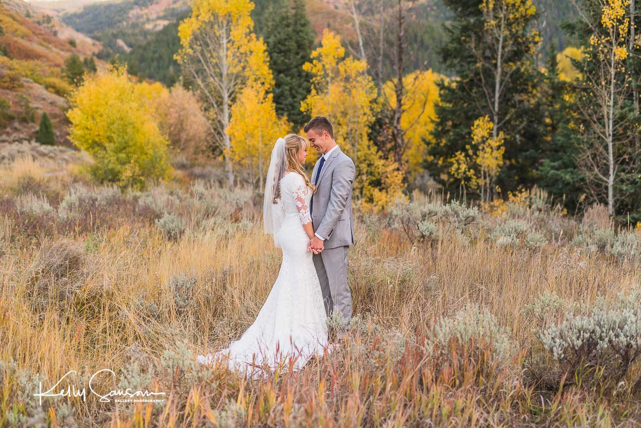 A bride and groom with foreheads touching and holding hands in front of beautiful aspen trees for bridal photography at Tibble Fork.