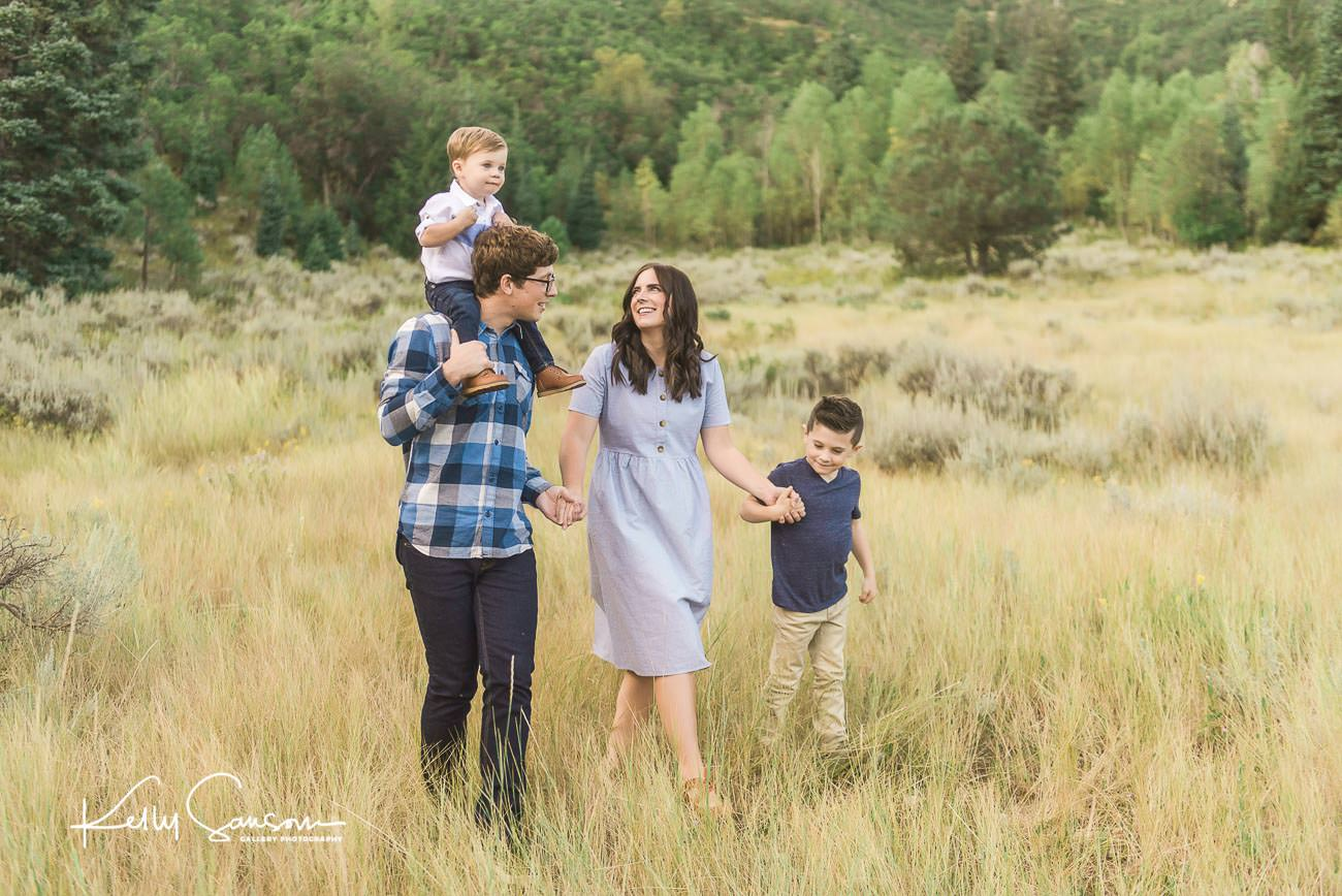 Family walking together holding hands and laughing through tall grasses for family photography at Tibble Fork.