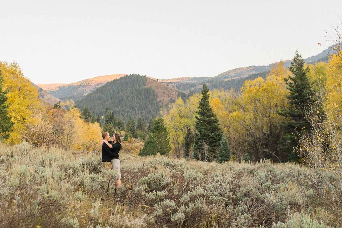 Couple snuggling together with aspens and pines as well as the rolling hills behind them for engagement photography at Tibble Fork.