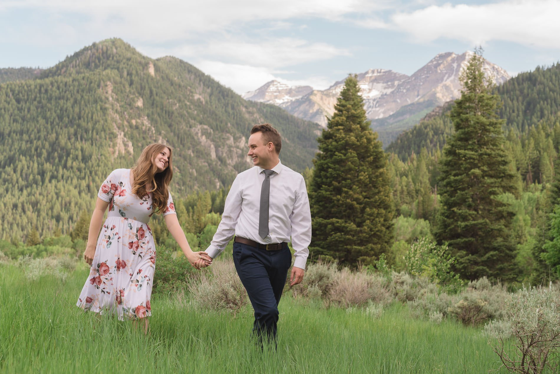 A couple walking through the brush hold hands and laughing with Mt Timpanogos and pines in the background for engagement photography at Tibble Fork.