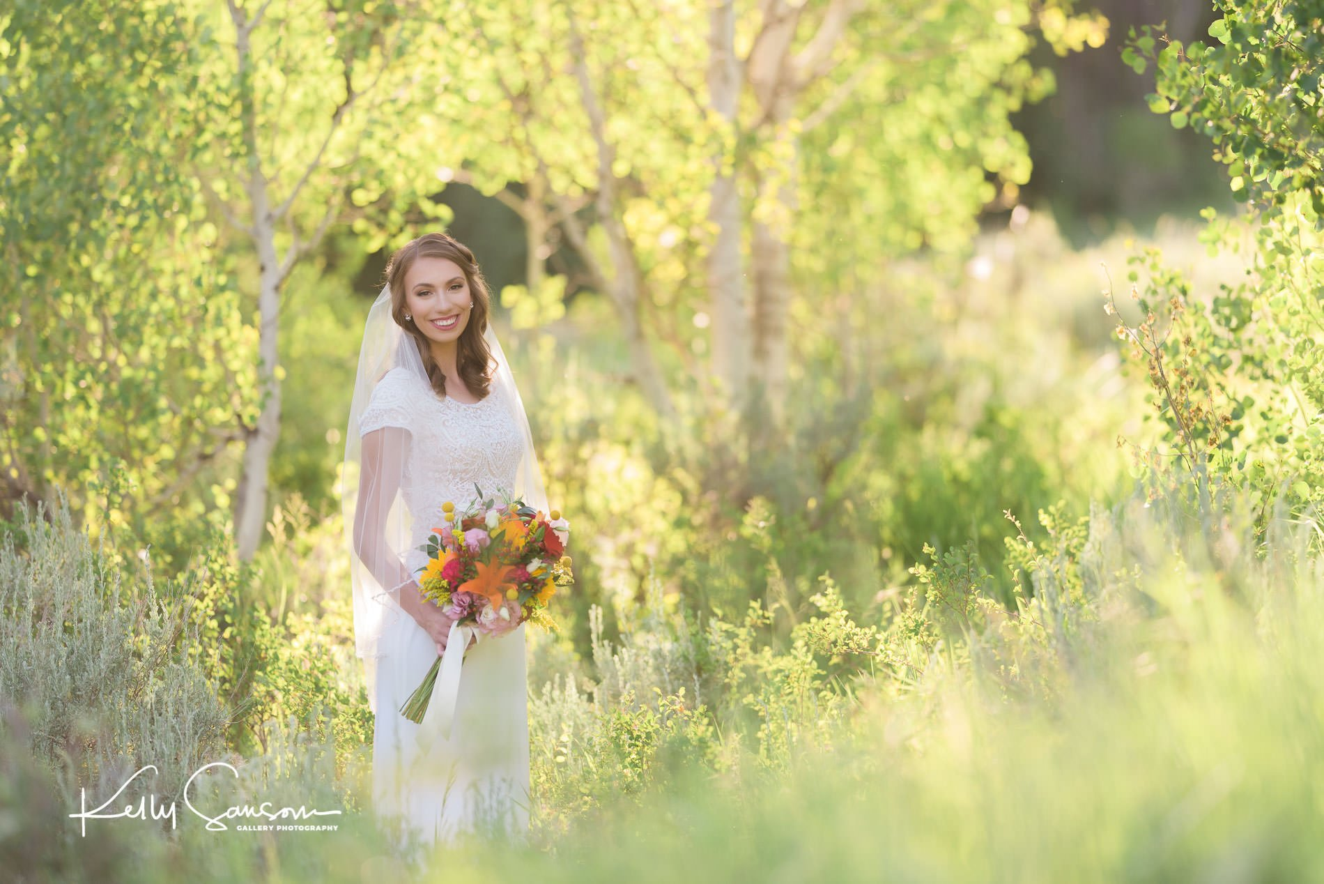 A bride holding her bouquet smiling with yellow aspen leaves behind for bridal photography at Tibble Fork.