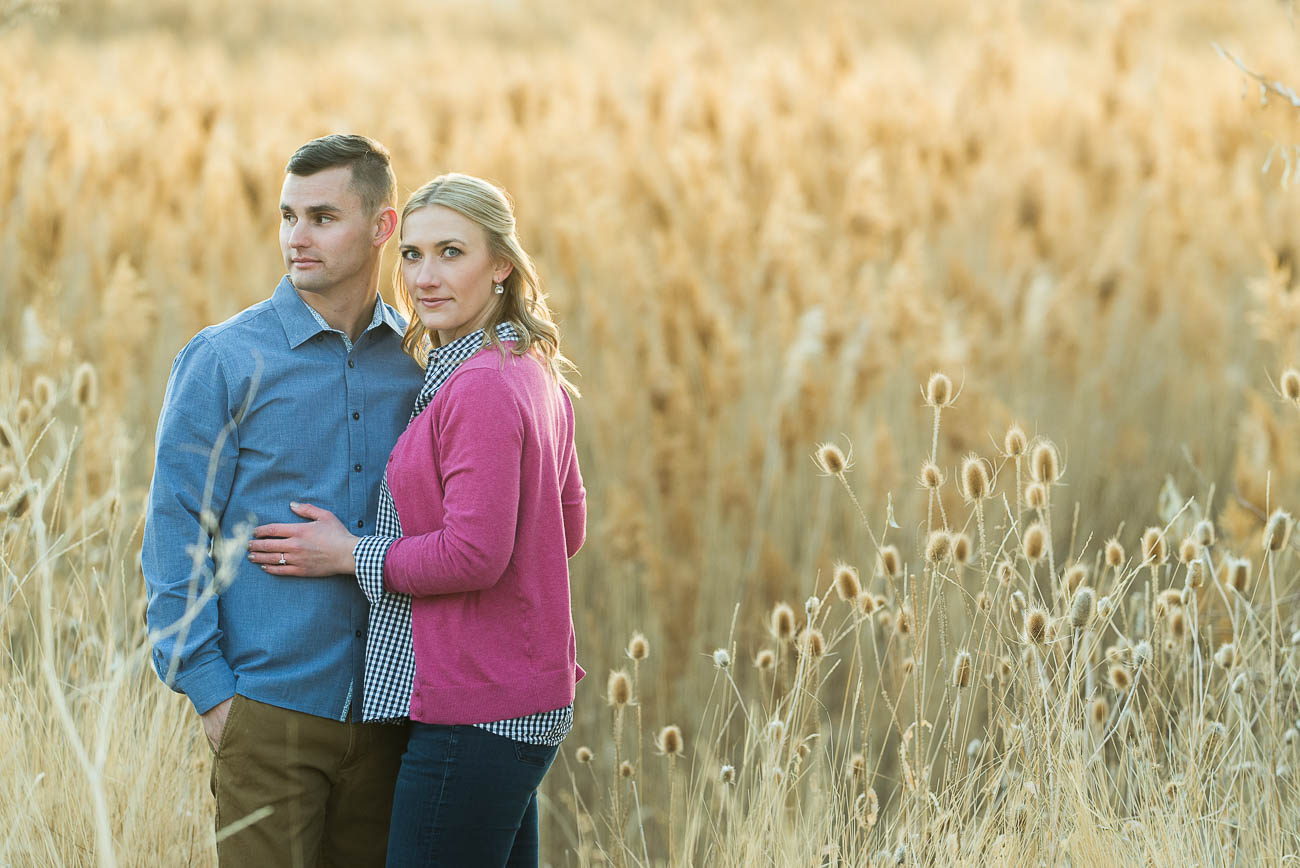 picture of woman looking at the camera while man looks off camera in tall grass in engagement photography at tunnel springs park.
