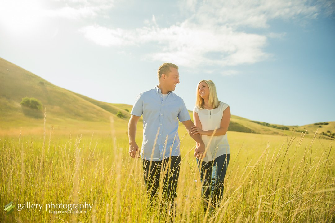 couple walking through the grasses holding hands for engagement photography at tunnel springs park.