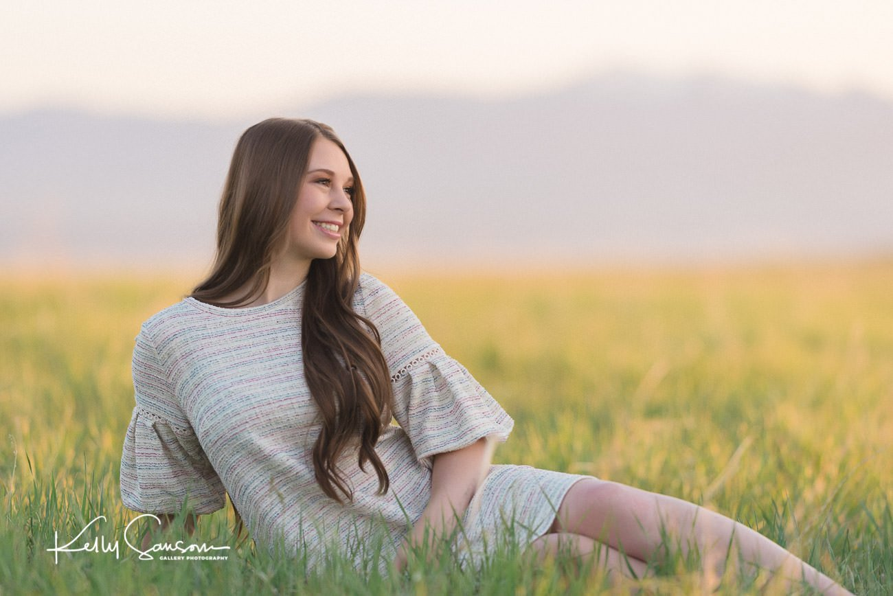 girl sitting in the grass in senior photography at tunnel springs park.