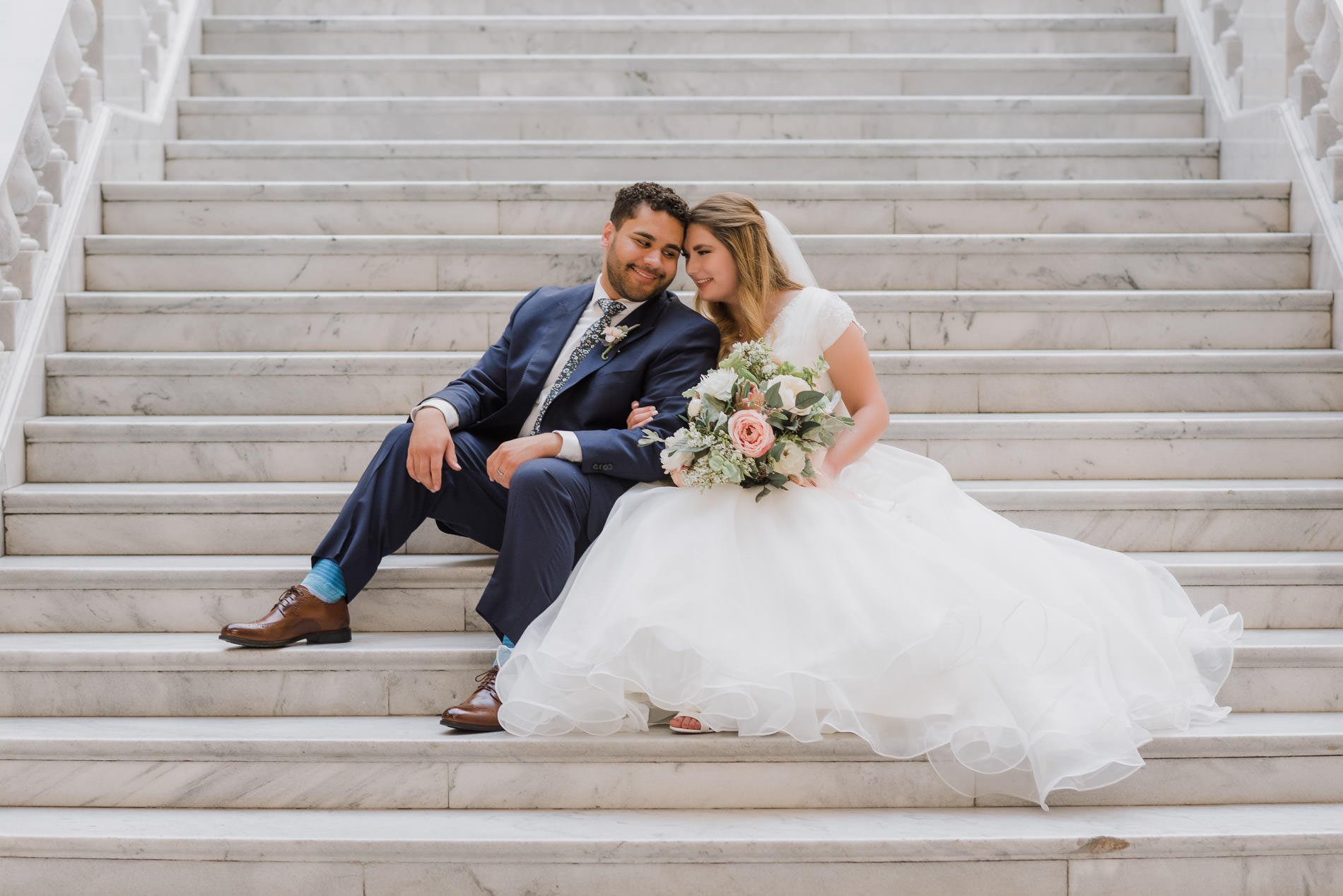 a bride and groom sitting on the steps snuggling for bridal photography at the utah state capitol