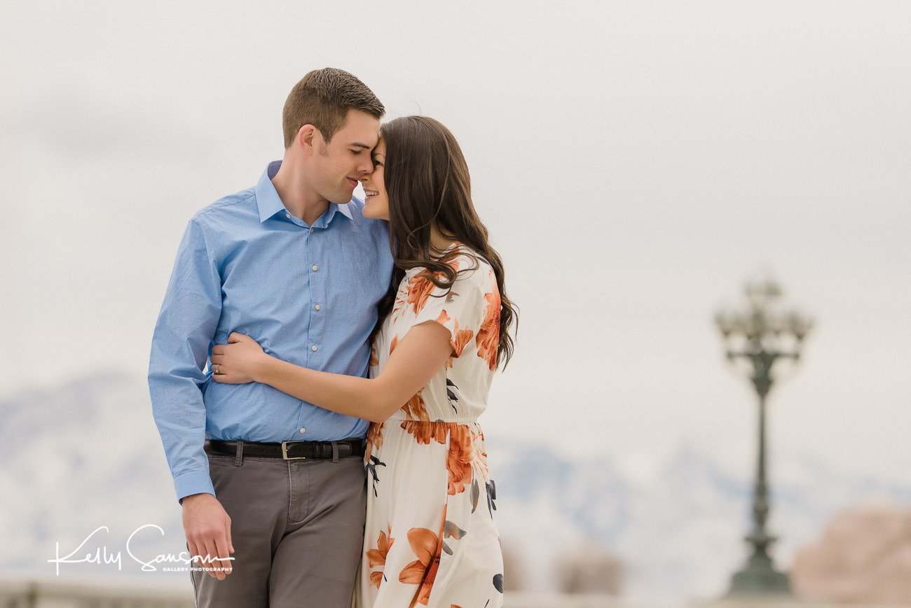 a couple walking and snuggling outside for engagement photography at the utah state capitol