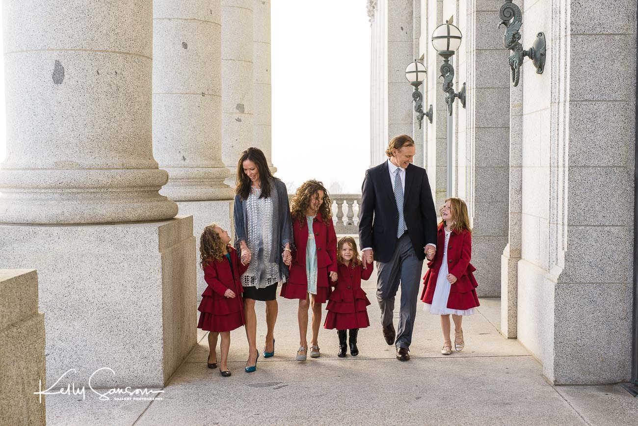 A family walking together amongst columns for family photography at the utah state capitol.