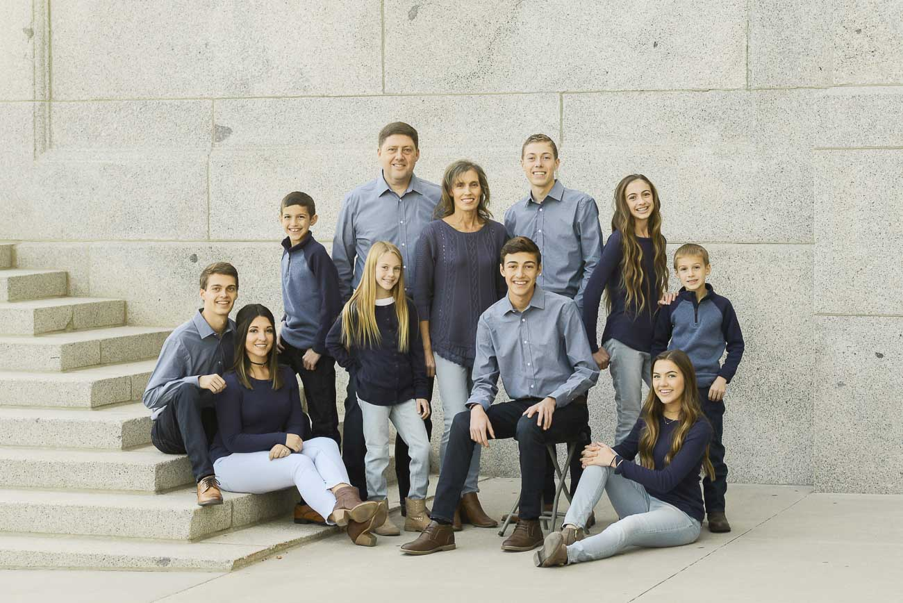 a large family posing together on stairs for family photography at the Utah State Capitol.