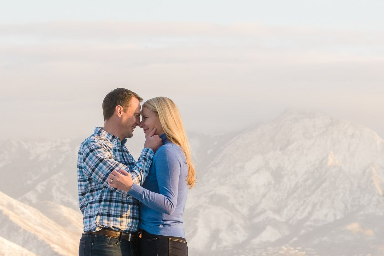 A couple snuggling with the mountains in the background for engagement photography at the Utah State Capitol.