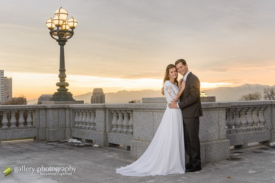 A couple posing together on a snowy evening by light post and a view of the city for bridal photography at the Utah State Capitol.